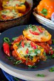 Two halves of stuffed bell peppers. On a dark plate royalty free stock photos