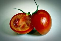 The two halves of the tomato. Tomato, cut into two slices on a white background royalty free stock image