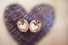 Two halves of walnut as heart on dark wooden table are visible through hole in shape of heart. royalty free stock photography