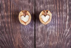 Two halves of walnut in shape of heart are lying on two part of stock photos
