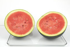 Two Halves of a Watermelon. A dark green organic watermelon cut in half Royalty Free Stock Photography