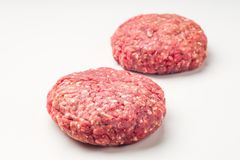 Two hamburger patties isolated on white background. Close up two  raw red meat burgers for hamburgers of minced ground beef or pork ready for cooking isolated on Royalty Free Stock Photo