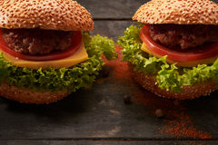 Two hamburger on a wooden table Royalty Free Stock Photography