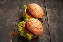 Two hamburger on a wooden table Royalty Free Stock Photos