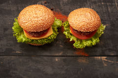 Two hamburger on a wooden table Royalty Free Stock Images