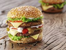 Two hamburgers on old wooden table. Stock Photo