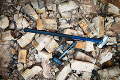 Two Hammers Breaks Down Wall. Rubber and Steel Hammers that demolish and break down brick wall brown and concrete. Broken Pieces. Chunks of Bricks. Crumble down Stock Image