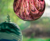 Two hand blown glass balls hanging in front of window Royalty Free Stock Photography