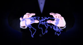 Two hand covered the glowing world map. Stock Photos