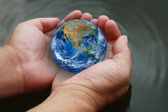 Two hand hold the earth on water ,including elements furnished b Stock Photo