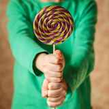 Two hand hold lollipop in the indoors, square Stock Image