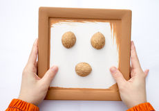 Two hand holding a frame with walnut. Stock Image