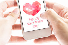 Two hand holding smartphone with pink polygon heart shape and Ha Royalty Free Stock Photo
