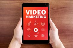 Two hand holding tablet with Video marketing and icon on screen stock image