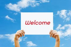 Two hand holds a sign for the  welcome. Two hand holds  sign for the  welcome Royalty Free Stock Photos
