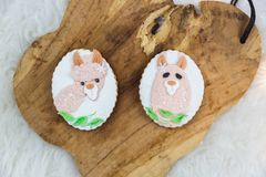 Two hand painted gingerbreads on a wooden background. The cute ilama shaped are painted on the gingerbread. Close-up royalty free stock images