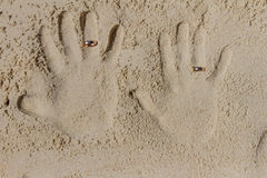 Two hand prints with wedding rings on sand beach, outdo Stock Photos