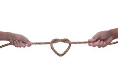 Two hand pulling a rope with heart shape Stock Photo