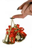 Two handbells hanging on a finger. Royalty Free Stock Photography