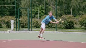 Two-Handed Backhand from the right court's coner. Powerfull tennis shot. Slow Motion. The player shows his tennis skills. This session is full of many different stock video