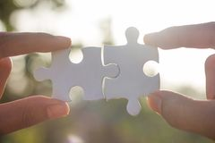 Two-handed jigsaw puzzle piece connectors, green bokeh background, Joint Business Concepts stock photo
