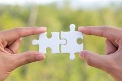 Two-handed jigsaw puzzle piece connectors, green bokeh background, Joint Business Concepts stock image