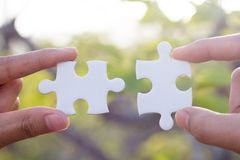 Two-handed jigsaw puzzle piece connectors, Natural green background, Joint Business Concepts royalty free stock images