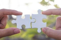 Two-handed jigsaw puzzle piece connectors, Natural green background, Joint Business Concepts stock images