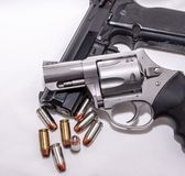 Two handguns, a 40 caliber pistol and a 357 magnum revolver with 40 caliber bullets. On a white background stock photos
