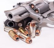 Two handguns, a 40 caliber pistol and a 357 magnum revolver with 40 caliber bullets. On a white background stock image