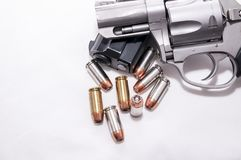 Two handguns, a 40 caliber pistol and a 357 magnum revolver with 40 caliber bullets. On a white background stock images