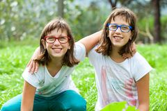 Two handicapped twins embracing outdoors. Royalty Free Stock Images