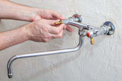 Two handle kitchen faucet repair, plumber hands replacement  tap Royalty Free Stock Photo