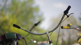 Two handlebars focus in, in summer sunny evening. Pan horizontal. Two handlebars focus in, in summer sunny evening.  One bicycle with a basket. Pan horizontal stock footage
