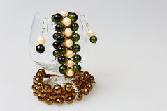 Two handmade bracelets with earrings in a glass of cognac on iso Stock Images