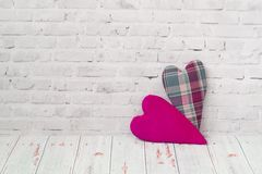 Two handmade hearts from checkered fabric stand on a light brick background, and on a light background of a wooden table . The. Two handmade hearts from stock images