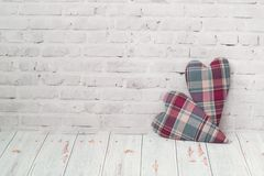 Two handmade hearts from checkered fabric stand on a light brick background, and on a light background of a wooden table . The. Two handmade hearts from stock photos