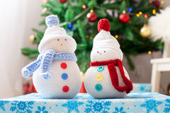 Two handmade snowmen with Christmas background on white fur Stock Image