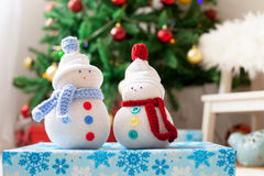 Two handmade snowmen with Christmas background on white fur Royalty Free Stock Photo