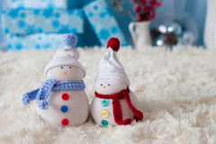 Two handmade snowmen with Christmas background on white fur Royalty Free Stock Photography