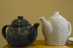 Two handmade teapots on a wooden shelf in the market. White ceramic teapot in the black dot. Dark teapot. stock images