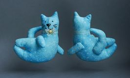 Flying blue cats. Two handmade toys with a bow around his neck. From a cloth with a pattern, soft. Kind, pleasant, smiling cats Stock Photos