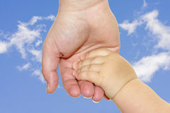 Two hands. Two holding hands on blue sky Stock Images