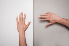 Two hands against a green and white background Stock Photo