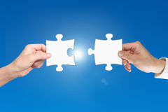 Two hands assembling jigsaw puzzle pieces. Man and woman two hands assembling jigsaw puzzle pieces, with blue background. Teamwork concept Stock Photos