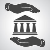 Two hands with badge with black bank icon on a grey background - Stock Photos