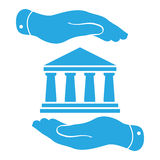 two hands with badge with white bank icon on a blue background - Royalty Free Stock Photography