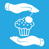 Two hands with badge with white cake icon and cherry on a blue b Royalty Free Stock Photography