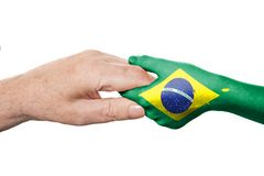Two hands and Brazilian flag Stock Photo