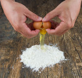 Two hands break egg on wooden surface on a heap of flour Stock Photos